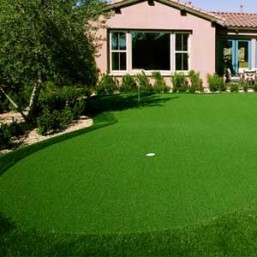 Artificial backyard putting green with pink house