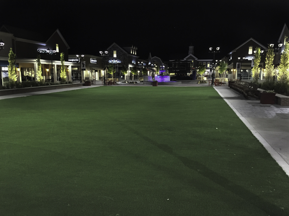 Artificial turf courtyard in middle of shopping center at night