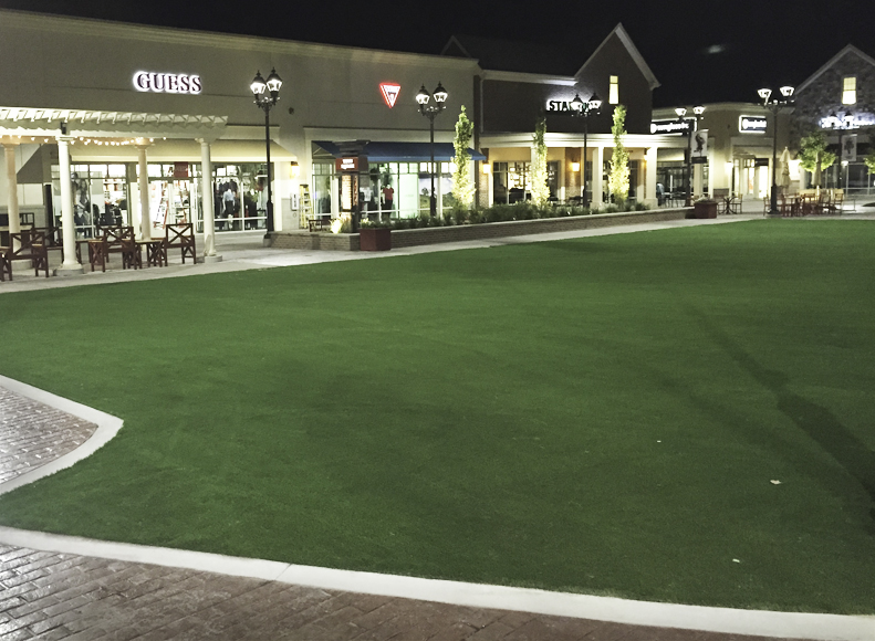 Artificial grass courtyard at night at outdoor shopping mall