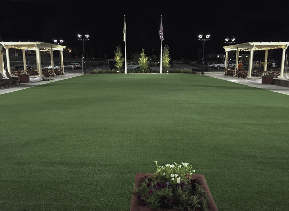 Courtyard with artificial grass facing parking lot with flags and lights