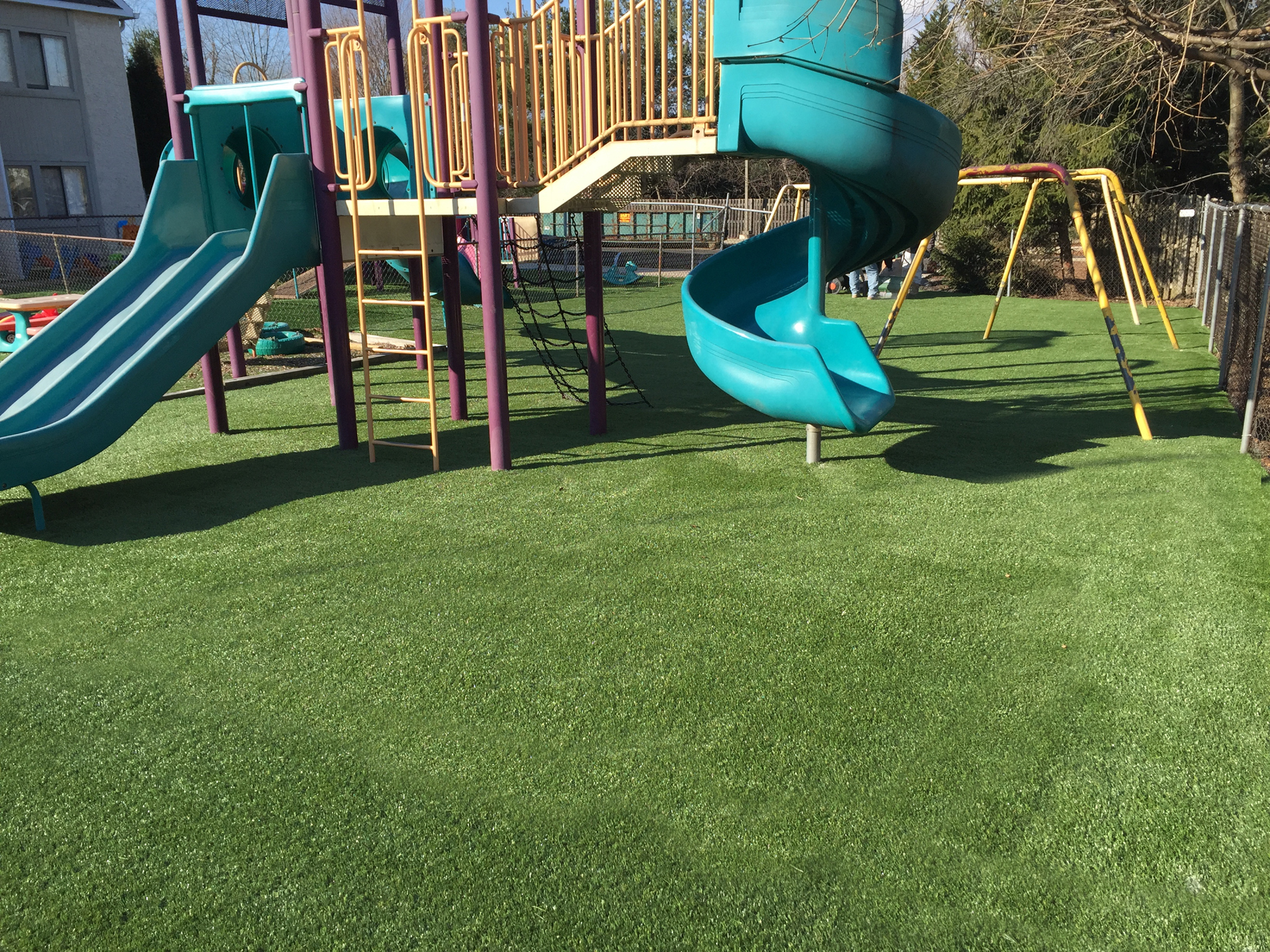 Colorful outdoor play equipment with artificial turf surface