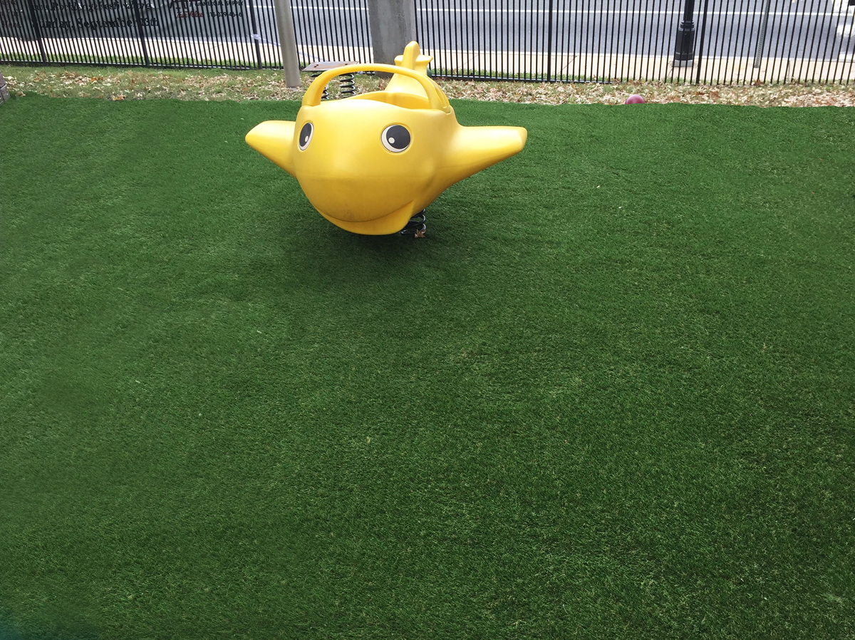 Close-up view of yellow plane totter and fake grass surface