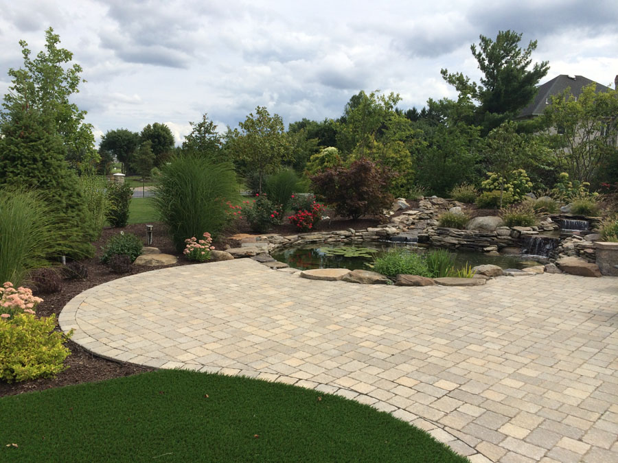 Custom built pond next to an artificial grass patio in New Jersey