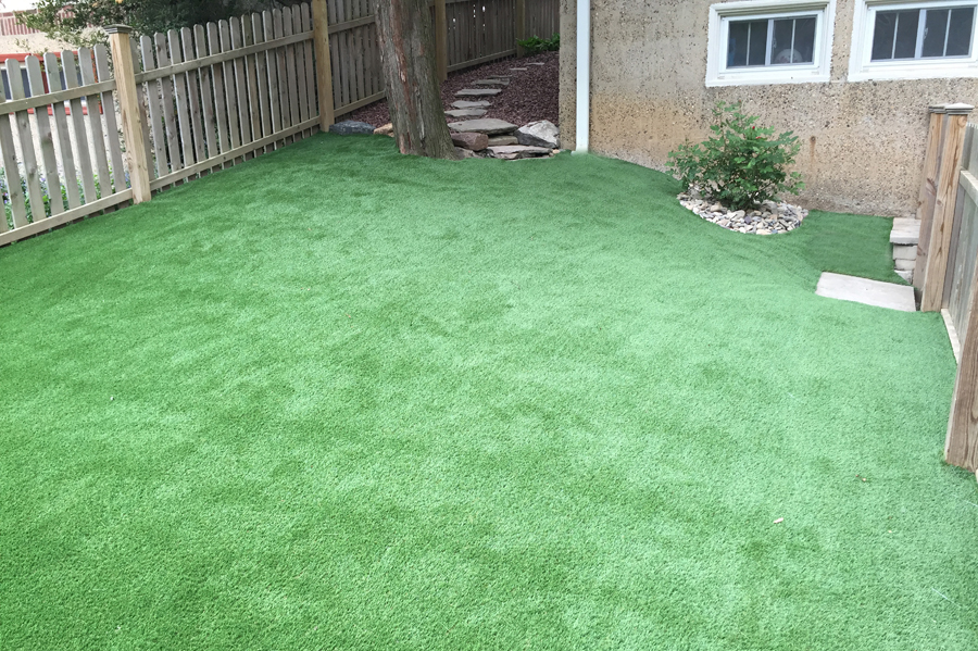 Sloping artificial lawn in the backyard of a New Jersey home