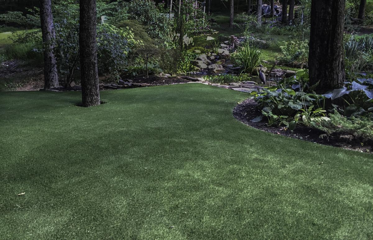 Artificial grass lawn in the middle of a lush forest in NJ
