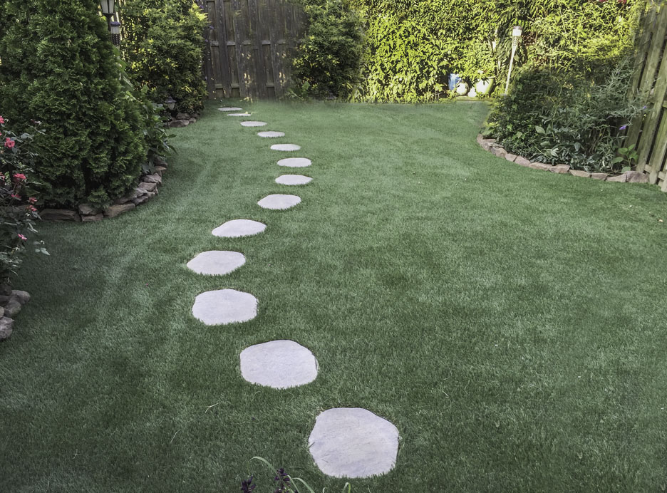 Stone pathway winding through a synthetic lawn in PA