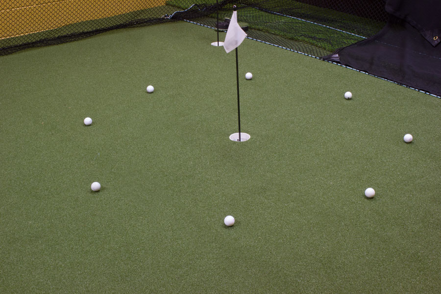 Golf balls circled around a pin on an indoor putting green in PA