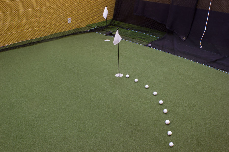 Golf balls lined behind a pin on an indoor putting green in PA