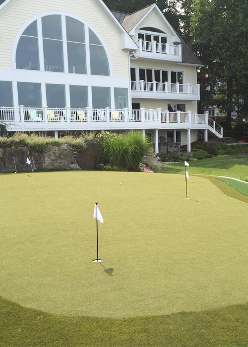 Yellow house overlooking a custom putting green in NJ