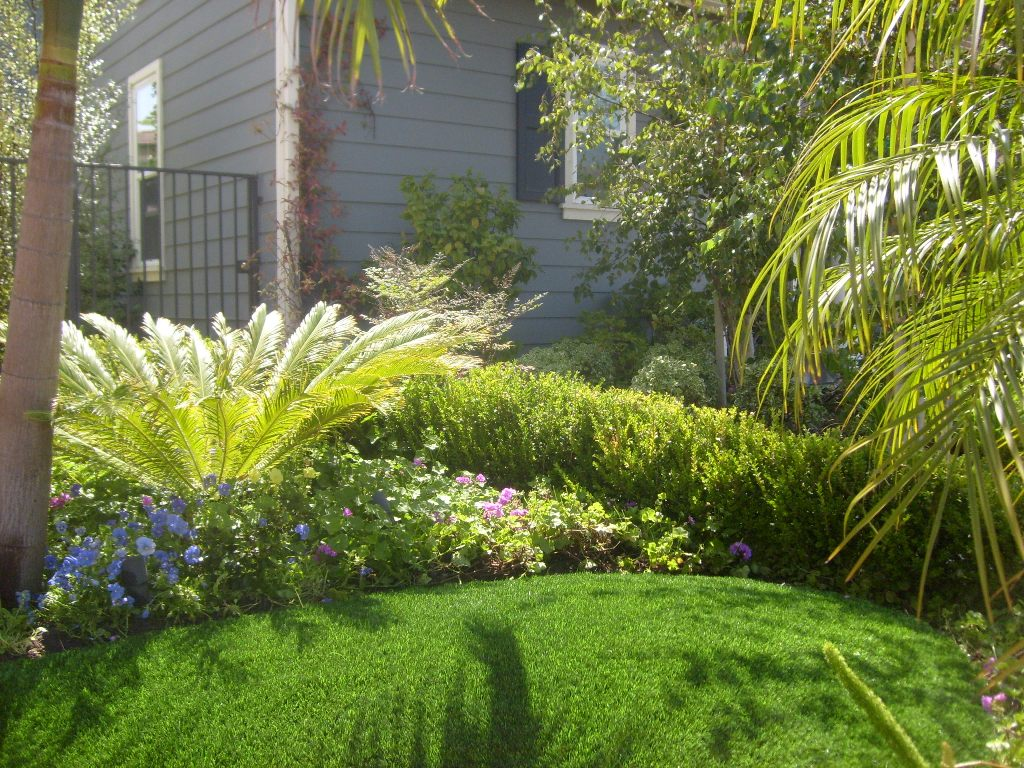 Synthetic grass yard lined by a colorful garden